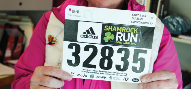 Trin Cramer-Eves holds up the Shamrock Run bib number issued to Shell Martin. Cramer-Eves will wear it at the Shamrock Run in Martin's honor