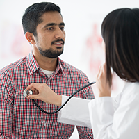 Patient and doctor using stethoscope